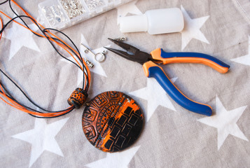Assembly of handmade tribal jewelry from polymer clay. Creativity background.Working process.