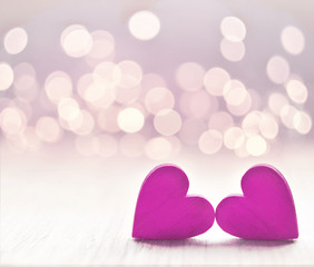 Hearts on a wooden table and background is a bokeh.