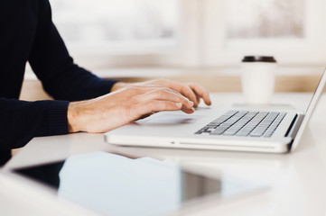 Businessman using laptop computer. Male hands typing on laptop keyboard