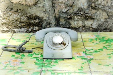 Close up of an old gray telephone on the table with floral design. Vintage telephone with rotary dial, outdoor