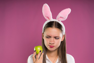girl with funny pink ears looks suspiciously at a green apple in her hand