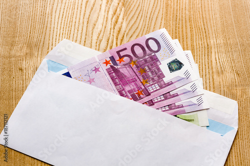 euro banknotes in a white envelope on a wooden background bribe