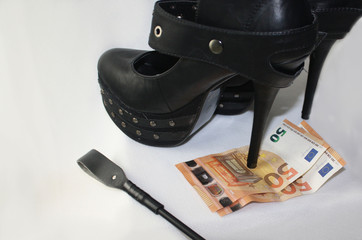 Dominance bdsm prostitute concept, high heel black shoes and leather whip and two fifty euro banknotes
