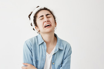 Stressful puzzled young female model with dark wavy hair wears do-rag and denim shirt being in panic as doesn`t know what to wear on date with boyfriend, troubled, frowns face and cries.