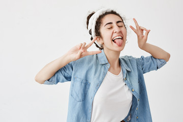 Happiness, beauty, joy and youth. Young positive girl dressed in denim shirt over white t-shirt showing v sign, smiling broadly, with closed eyes, sticking out her tongue, having good mood.