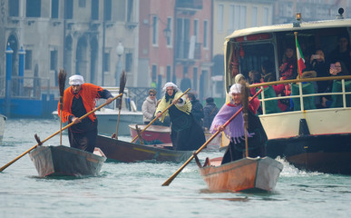 "Men dressed as ""La Befana"", an imaginary old woman who is thought to bring gifts to children during the festival of Epiphany, row boats down the Grand Canal in Venice"