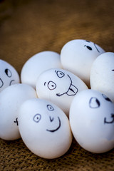 Close up of eggs with funny faces drawn on them.