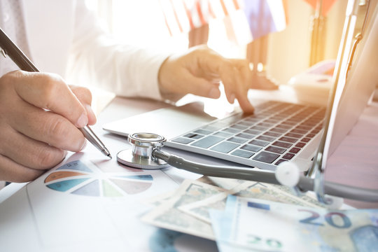 Doctor working on laptop computer with report analysis and money about Healthcare costs and fees in medical hostpital office. Focus stethoscope on table. Healthcare budget and business concept