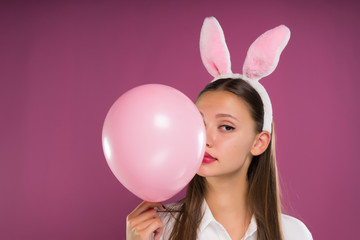 lovely girl with pink ears on her head holds a ball in her hands, isolated