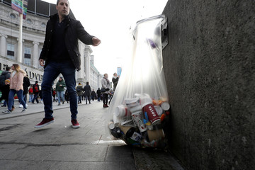 A pedestrian throws a discarded item into a bag containing paper cups alongside other rubbish on the Southbank, in London