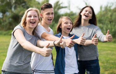 teenagers show their thumbs up