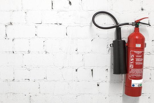 Feuerlöscher an Backsteinwand montiert