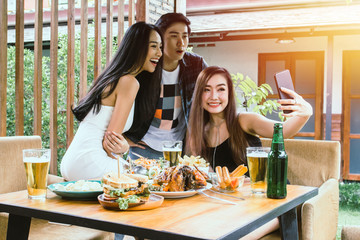 Two Asian women and one men hand holding mobile phone Taking pictures with  food on table