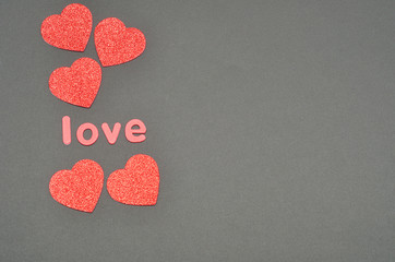The word love on a black background decorated with five red glitter hearts