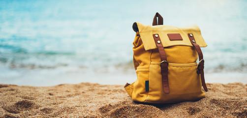 Hipster hiker tourist yellow backpack closeup on background blue sea enjoying sunset ocean horizon, blurred panoramic seascape sunrise blank mockup, traveler relax holiday concept, sunlight