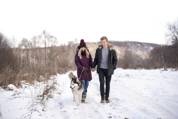 A young couple go on a winter road with the husky In the background the mountain.