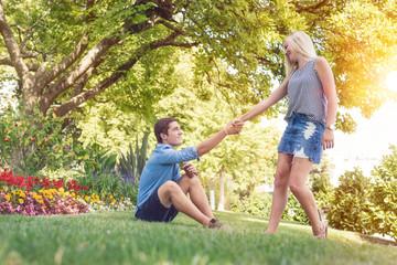 Junge Frau hilft ihrem Freund vom Rasen im Park hoch