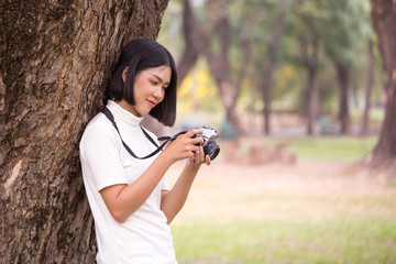 Attractive Asian woman holding retro camera with smiling, Woman using camera at outdoor place.