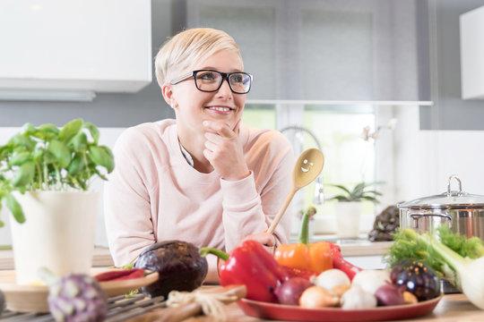 Junge hübsche Frau in ihrer Küche lächelt und überlegt, welches Gemüse sie kochen soll