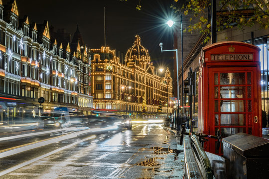 traffic jam in street of London at night during christmas holidays with a historical phone cab