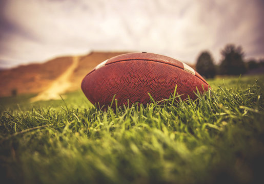 a brown american football lying on green grass in a field with a hill and trees in the background toned with a retro vintage instagram filter app or action effect