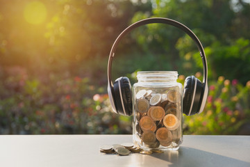 Coins in jar with money stack and headphone, Concept finance, accounting, business and saving investment.