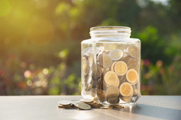 Coins in jar with money stack, Concept finance, accounting, business and saving investment.