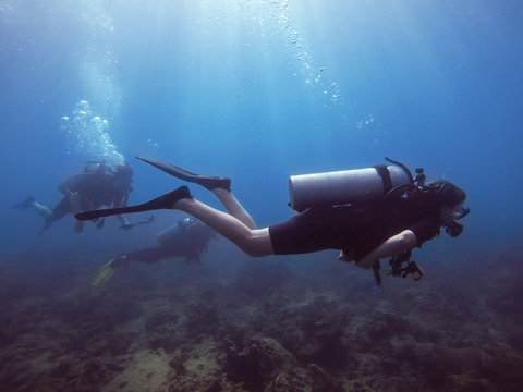 Thailand, Pang-nga, Kho Lak, 3rd Jan'18. Kho Na Yak. Student for diving open water course with diving gear (equipment) practicing divning in the deep blue sea surrounding by brown corals. Editorial.