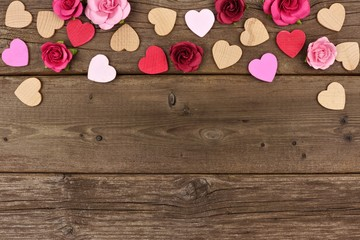 Valentines Day top border of wooden hearts and paper roses against a rustic wood background with copy space.