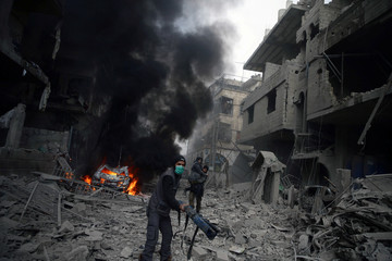 Syria Civil Defence member carries wounded woman in Hamoria, Eastern Ghouta, Damascus