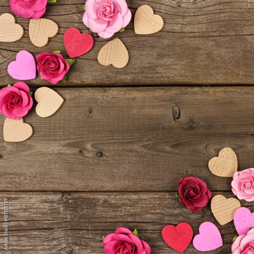 Valentines Day Corner Frame Of Wooden Hearts And Paper Roses Against A Rustic Wood Background With