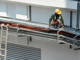 Electrical contractor installing electrical cable tray at the construction site. Working at height wearing proper safety gear.