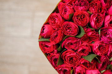 half image of round big romantic bouquet of red pion-shaped roses
