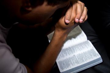 Hombre de rodillas hablando con Dios, con su Biblia abierta.