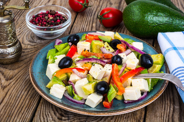 Vegetable salad with feta on wooden background