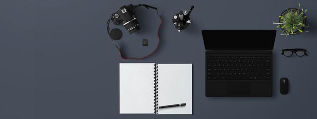 scrivania con notebook ,fotocamera e quaderno