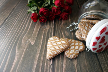 Valentines day concept with sweet heart shaped gingerbreads and flowers on wooden background