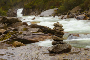 Arranged stones with a mountain river on backgrouud