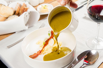 Cream of sorrel and green vegetables soup with quail egg, sour cream, mashed potatoes and crispy bacon being poured from a jug