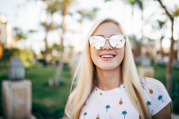 Close up portrait woman wearing sunglasses posing with palm tree