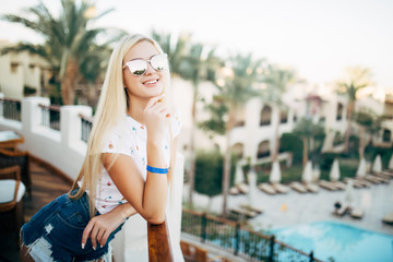 Portrait of beauty summer girl in sunglasses on balcony of hotel room look at palms garden on background