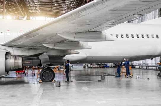 Several people wash the aircraft in the hangar for maintenance, view of the chassis, wing and tail.
