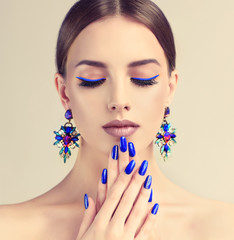 Beautiful model girl with blue  manicure on nails . Fashion makeup and cosmetics . Large earrings  jewelry .