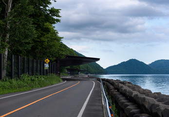 Scenic road bending around the beautiful clear mountain lakes of Shikotsu-Toya National Park, Hokkaido, Japan