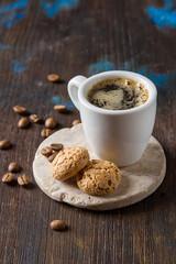 Italian homemade espresso coffee in a white mug. Dark background.