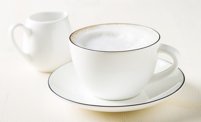 Italian homemade espresso coffee in a white mug. Light background.