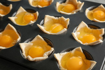 Baking mold with raw eggs in dough, closeup