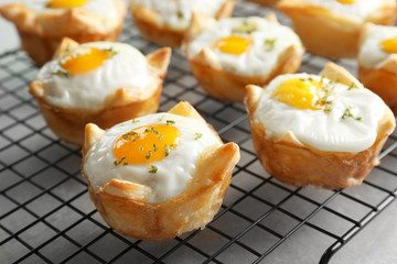 Tasty baked eggs in dough on cooling rack