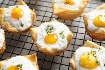 Tasty baked eggs in dough on cooling rack