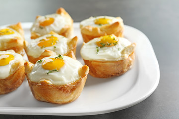 Tasty baked eggs in dough on plate, closeup